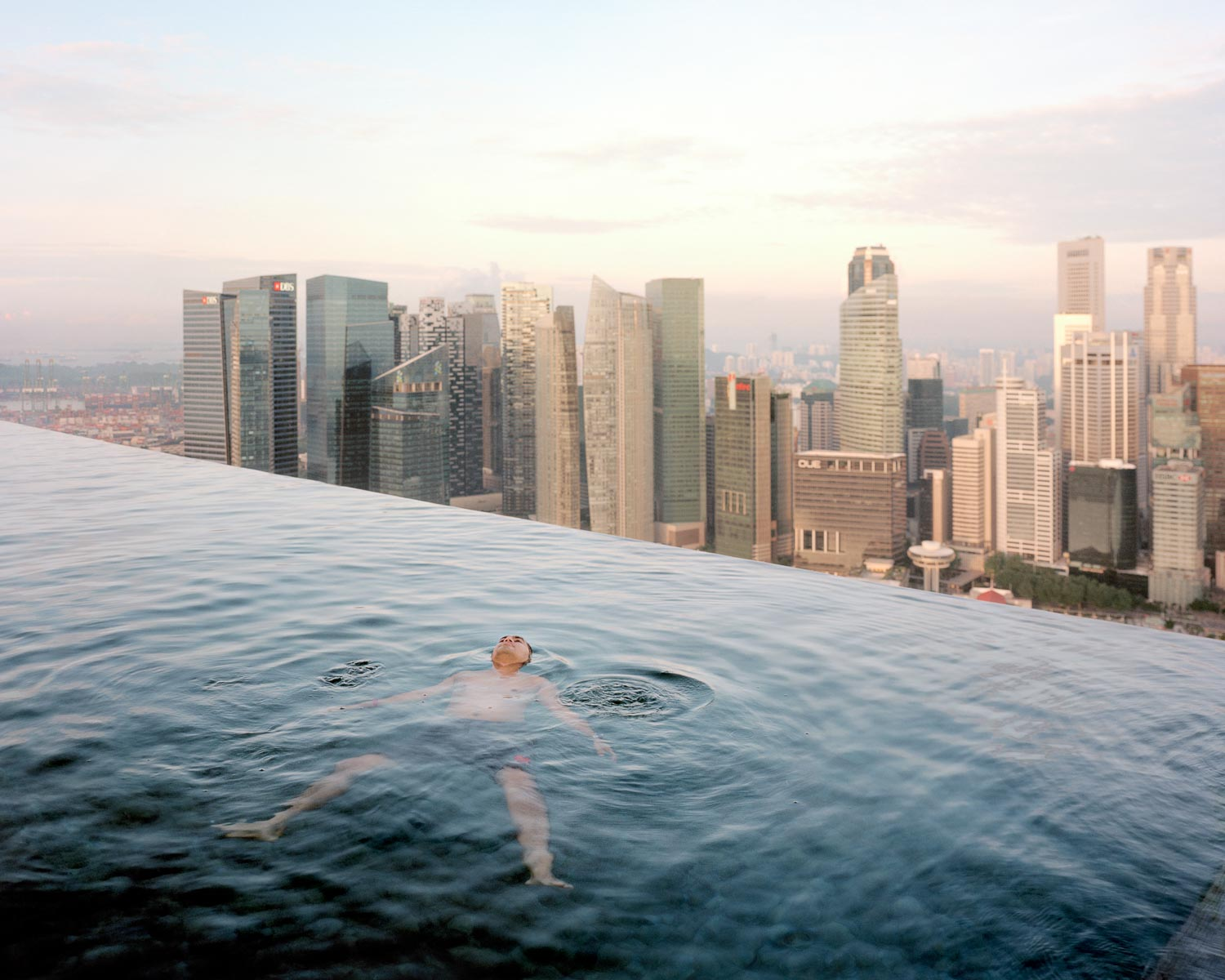 A man floats in the 57th-floor swimming pool of the Marina Bay Sands Hotel, with the skyline of the Singapore financial district behind him. 2013 Paolo Woods & Gabriele Galimberti - INSTITUTE